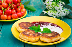 Cheese pancake with jam and fresh cherries. Wooden turquoise background. Top view. Close-up Stock Photo