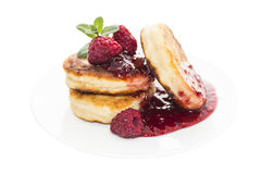 Cheese pancake with raspberries on plate. Cheese pancake is a flat cake, often thin, and round, prepared from a starch-based batter that may also contain eggs Stock Photos