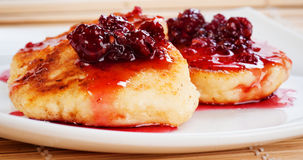 Cheese pancakes. With raspberry jam on white plate Stock Images