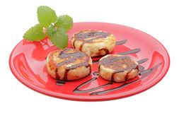 Cheese pancakes with chocolate syrup. On red plate Stock Photos