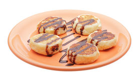 Cheese pancakes with chocolate syrup. On orange plate Stock Image