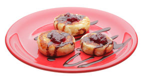 Cheese pancakes with chocolate syrup and jam. On red plate Stock Images