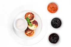 Cheese pancakes decorated with mint, served with sour cream and assorted jam on white background stock image