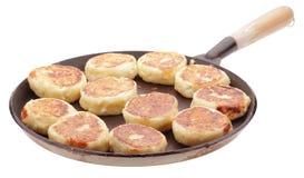 Cheese pancakes on pan. Isolated on white Stock Photos