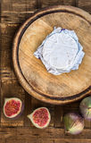 Cheese in paper on old circular cutting wooden board with slices of figs Stock Photography
