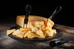 Cheese parmesan with a set of knives on  round slate board in style  rustic. Cheese parmesan with a set of knives on a black round slate board in style a rustic Stock Photo
