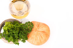 Cheese, parsley sprig and a glass of white wine on a white backg Royalty Free Stock Images