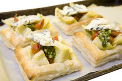 Cheese Pastries. Delicious pastries with artichoke, melted blue cheese and other roasted vegetables on a bed of rocket and tomato Royalty Free Stock Photos
