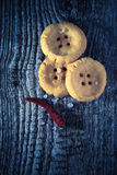 Cheese pastry shape like a button with seasalt and dry red hot c. Hili pepper on old light grey wooden table. Selective focus. Shallow depth of field. Toned Royalty Free Stock Photography