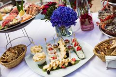 Cheese with pear and strawberries lie on plate. Next to seafood on table Stock Image