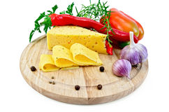 Cheese with pepper and herbs on a round board Stock Photography
