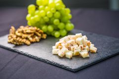 Cheese pieces juicy grapes and walnuts on slate board royalty free stock photos
