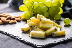 Cheese pieces juicy grapes and walnuts on slate board royalty free stock photography