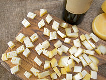 Cheese pieces and wine tasting. On rustic hessian, jute, burlap. Stock Photo