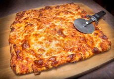 Cheese Pizza. Delicious Italian cheese pizza on cutting board with slicer Royalty Free Stock Photography