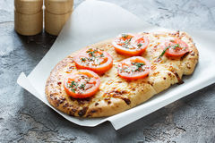 Cheese pizza with tomatoes, herbs and spices on a concrete backg Stock Images