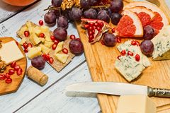 Cheese plate appetizer. Variety of gourmet cheese with fruits and nuts - ideal wine snack or appetizer in europe style. Served on rough wooden table in rural Royalty Free Stock Photo