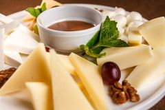 Cheese plate Assortment of various types of cheese and honey on white plate.  stock images