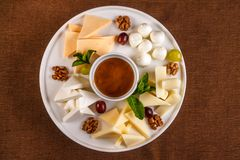 Cheese plate Assortment of various types of cheese and honey on white plate.  royalty free stock photos