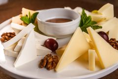 Cheese plate Assortment of various types of cheese and honey on white plate.  stock photos