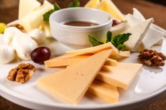 Cheese plate Assortment of various types of cheese and honey on white plate.  stock photography