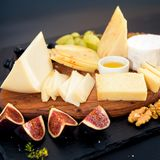 Cheese plate. Assortment of cheese with walnuts, almonds, grapes, figs, strawberries, blueberries and honey on a stone stock image
