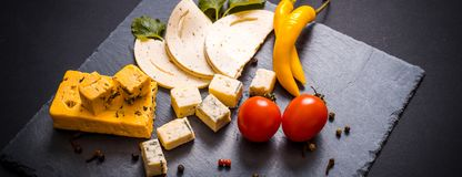 Cheese plate with blue cheese, brie, truffle hard cheese with grapes, figs, pears, honey, crackers, dried fruits and nuts on table stock images
