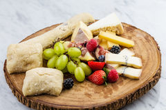 Cheese plate with bread grapes and strawberries Royalty Free Stock Photo