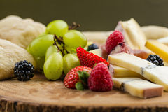 Cheese plate with bread grapes and strawberries Stock Image