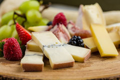 Cheese plate with bread grapes and strawberries Royalty Free Stock Images