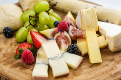 Cheese plate with bread grapes and strawberries Stock Images