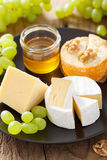 Cheese plate with camembert, cheddar, grapes and honey Stock Photo