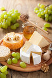 Cheese plate with camembert, cheddar, grapes and honey Royalty Free Stock Image