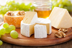 Cheese plate with camembert, cheddar, grapes and honey Royalty Free Stock Images