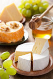 Cheese plate with camembert, cheddar, grapes and honey Royalty Free Stock Photos