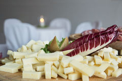 Cheese plate on catering buffet. Cubes of cheese, radicchio leaf and kiwi on wooden cutting board, on catering buffet, sliced salami and table in background Stock Photography
