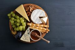 Cheese plate - cheese, grapes, plums, walnuts, bread sticks and stock photos