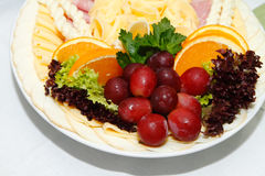 Cheese plate decorated with grapes and oranges Stock Image
