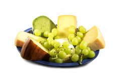 Cheese plate, different types of cheese and grapes on a blue plate isolated on a white background. Cheese plate, different types of cheese and grapes on a blue royalty free stock photo