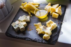 Cheese plate with different types of cheese, honey, fresh, delicious food menu photo. Cheese plate with different types of cheese, honey, fresh, served on table stock photography