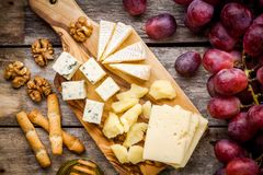 Cheese plate: Emmental, Camembert cheese, blue cheese, bread sticks, walnuts, grapes Royalty Free Stock Image