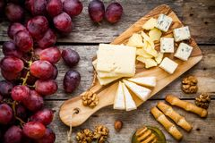 Cheese plate: Emmental, Camembert cheese, blue cheese, bread sticks, walnuts, hazelnuts, honey, grapes Stock Photo