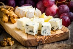 Cheese plate: Emmental, Camembert, Parmesan, blue cheese closeup, with bread sticks and grapes Stock Image