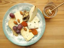 Cheese plate with fruits and nuts. Cheese plate. Five sorts of cheese. Cheddar, Talegio, Cheddar, aged in porter, Scamorza and cheese with blue mold Royalty Free Stock Photo