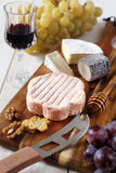 Cheese plate: French soft cheese, grapes and a glass of red wine Royalty Free Stock Photography