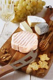 Cheese plate: French soft cheese, grapes and a glass of white wi stock images