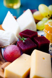 Cheese plate with fresh grape, honey, nuts,plum jelly, marmalade Royalty Free Stock Photos
