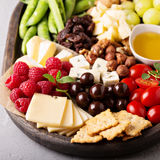 Cheese plate with fresh vegetables and fruits Stock Photo