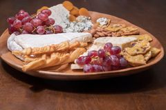 Cheese plate with fruit and nuts royalty free stock images