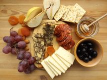 Cheese plate with fruit, snacks. Two types of cheese, chorizo sausage and olives Stock Photo